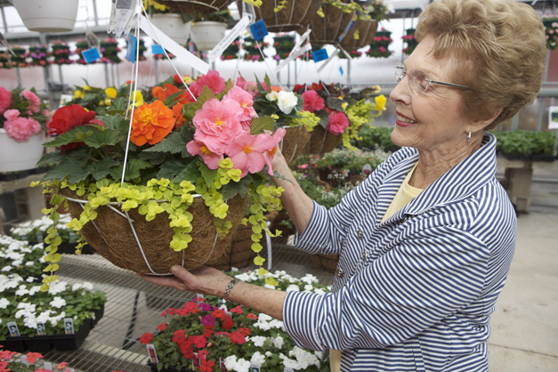 Esther Goebbert holding one of their custom-made hanging baskets.  Photographed by Julie Linnekin