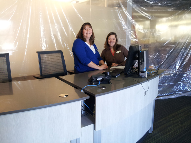 Two smiling librarians stand at a reference desk.
