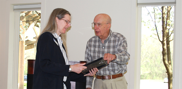 Photograph of librarian Kate Mills taking a framed certificate from trustee Dick Ryan in the library meeting room