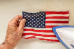 Pressing a small American Flag with an iron